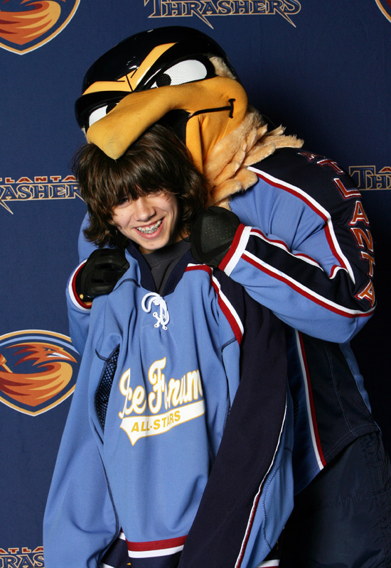 "The Thrashers loveable mascot ""Thrash"" chomps down on one of the kids."