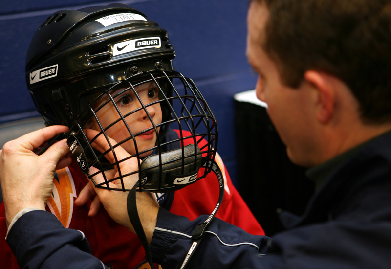 A dad helps his young son get ready for his debut on the ice at Philips.